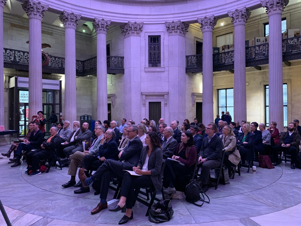 "A crowd gathers to celebrate George McAneny's sesquicentennial year at the Archive Project's October 17th event, ""Honoring the Spirits of McAneny,"" hosted at Federal Hall National Memorial. 